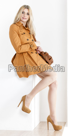 sitting woman wearing brown coat and