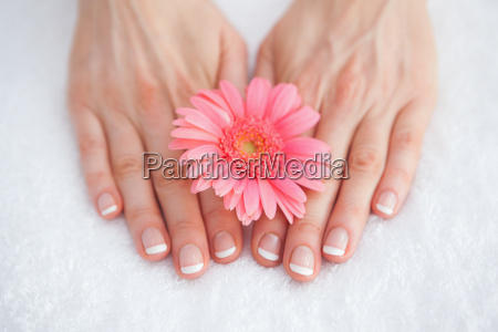 flower on french manicured fingers at
