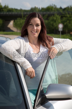 young woman leans against a car