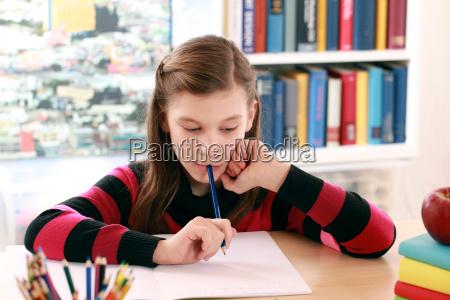 girl doing homework at desk