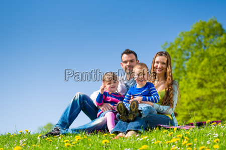 happy family sitting on summer meadow