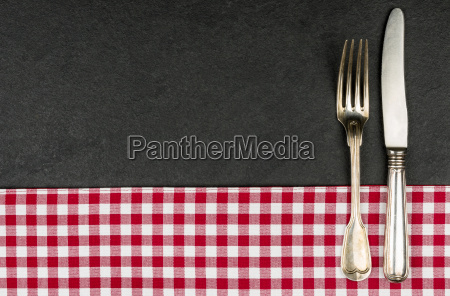 silver cutlery on a slate plate