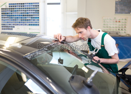 worker in glaziers workshop installs windshield
