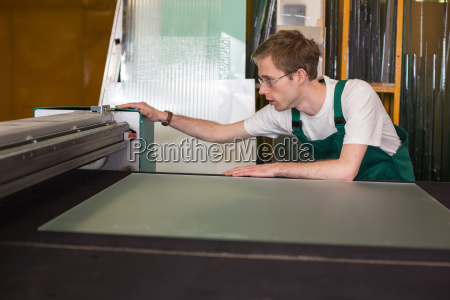 worker in glaziers workshop preparing a