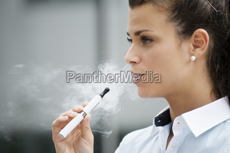 young woman smoking electronic cigarette outdoor