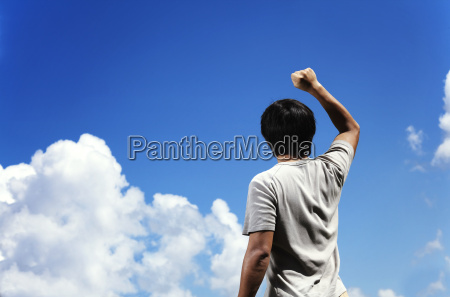 man clench fist facing the sky