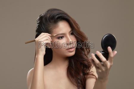 female asian drawing eye brow