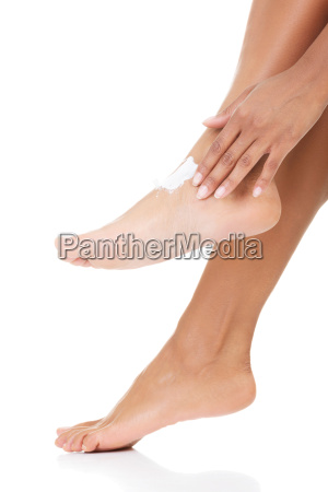 female hands treating feet with moisturizing