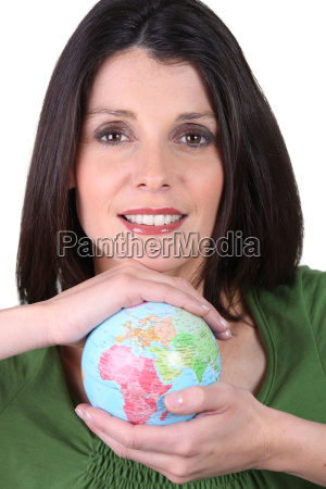 dark haired smiling woman holding globe