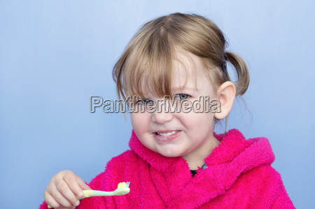 child cleaning teeth and smiling