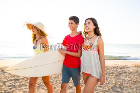 surfer girls with teen boy walking