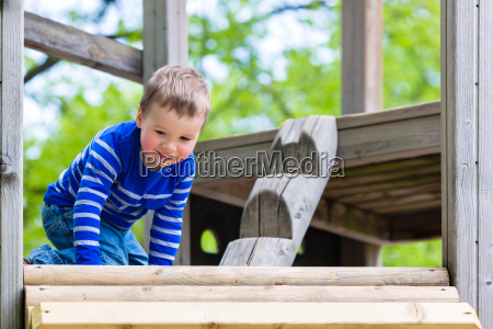 little kid plays on climbing frame