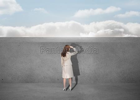 businesswoman watching a grey wall