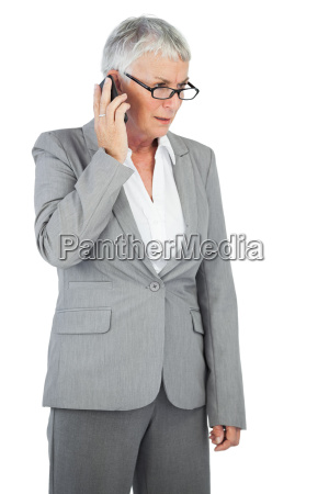 unsmiling businesswoman calling someone with her