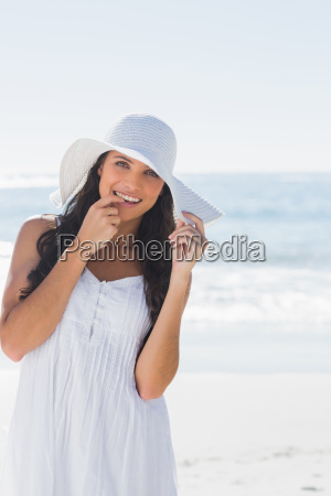 beautiful brunette in white sunhat looking