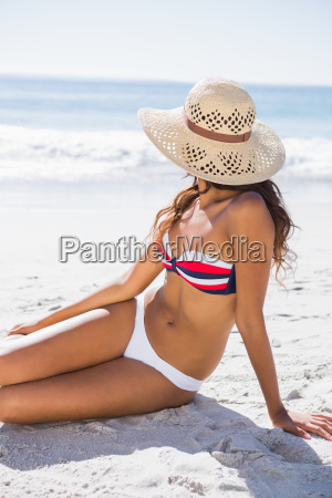 young tanned woman wearing straw hat