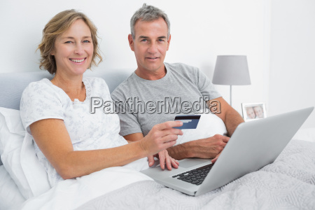 smiling couple using their laptop to