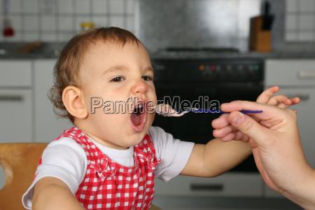 mother feeds baby with baby porridge