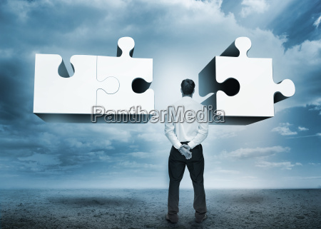 businessman, standing, looking, at, jigsaw, puzzle - 10040058