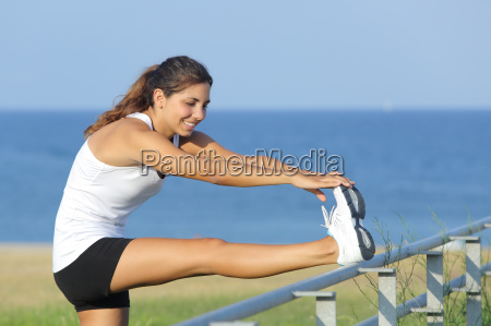 beautiful sportswoman stretching with the sea