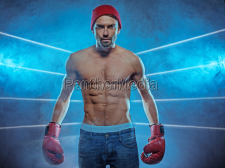 young athletic boxer in a smoky