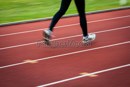 young, woman, running, at, a, track - 10147169