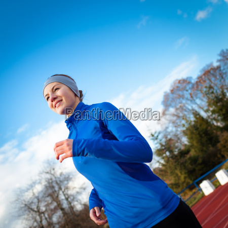 young, woman, running, at, a, track - 10147215