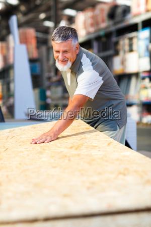 senior, man, buying, construction, wood, in - 10148087