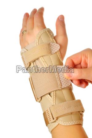 female wearing wrist brace over white