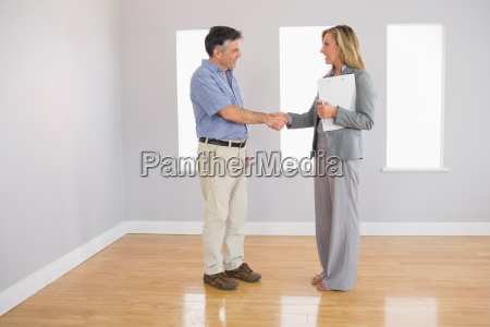 serious realtor shaking the hand of