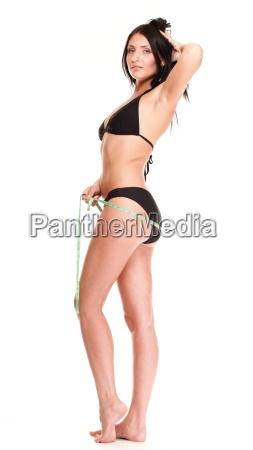 brunette girl bikini measuring waistline tape