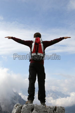 a climber spreads his arms to