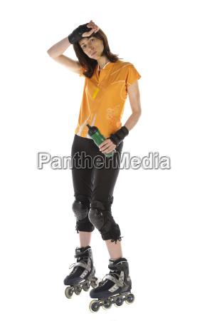 sportswoman with inline skates drinks water