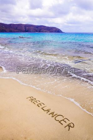 word freelancer written in sand on