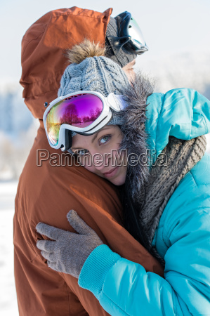 young couple embracing winter countryside ski
