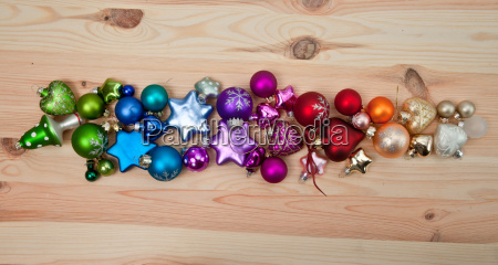 colorful christmas baubles on wooden background