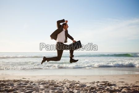young businessman jumping on the beach