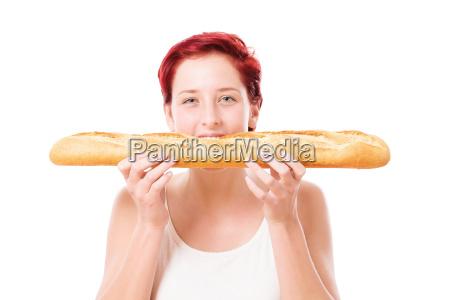 woman bites across into a baguette