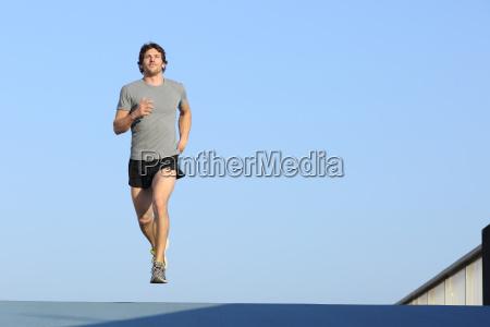 jogger running towards camera on blue