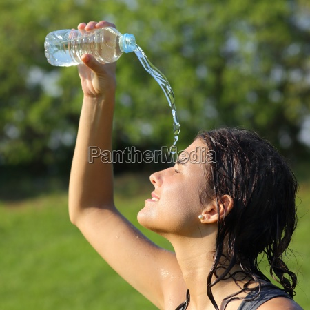 beautiful woman throwing herself water from