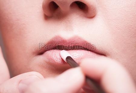 makeup girl applying lipgloss lipstick on