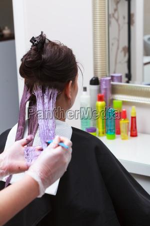 applying hairdresser color female customer at