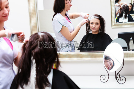 applying hairdresser color female customer at