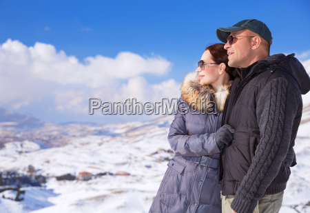 happy couple in snowing mountains