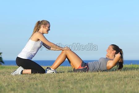 two sportswomen doing crunches