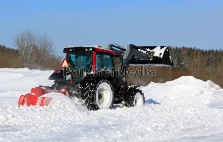 tractor plowing snow on a yard