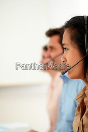 young attractive callcenter people using earphone