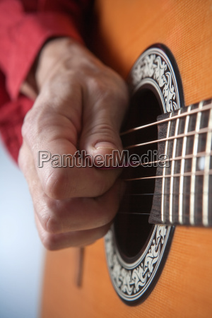 hands of a musician playing acoustic