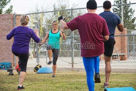 woman leading four adults in exercise