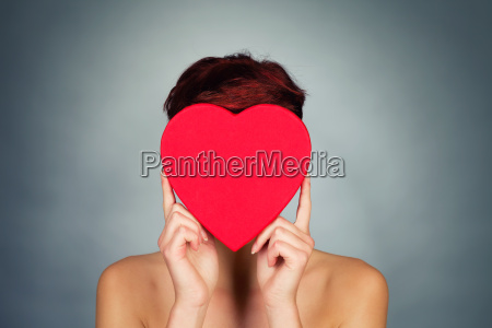woman holds red heart in front